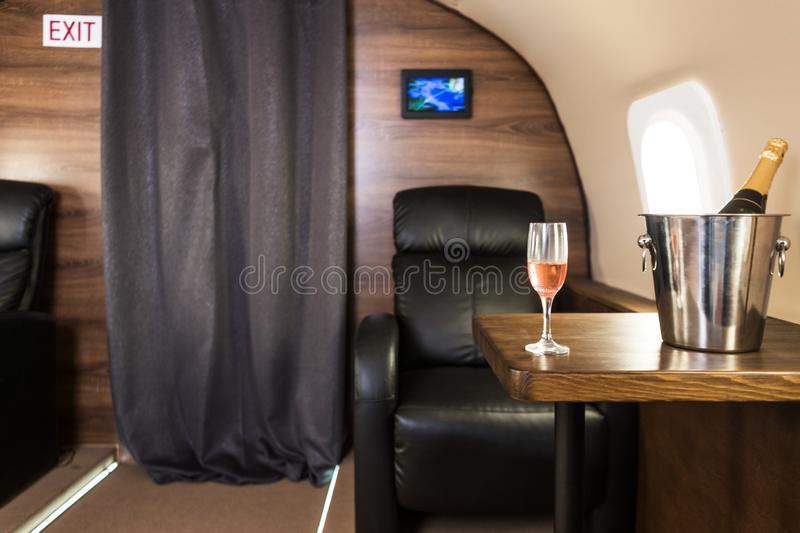A glass of champagne in the interior of a private jet. Flying first class.  stock images