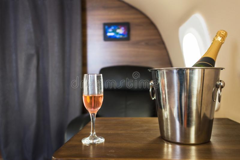 A glass of champagne in the interior of a private jet. Flying first class.  royalty free stock photo
