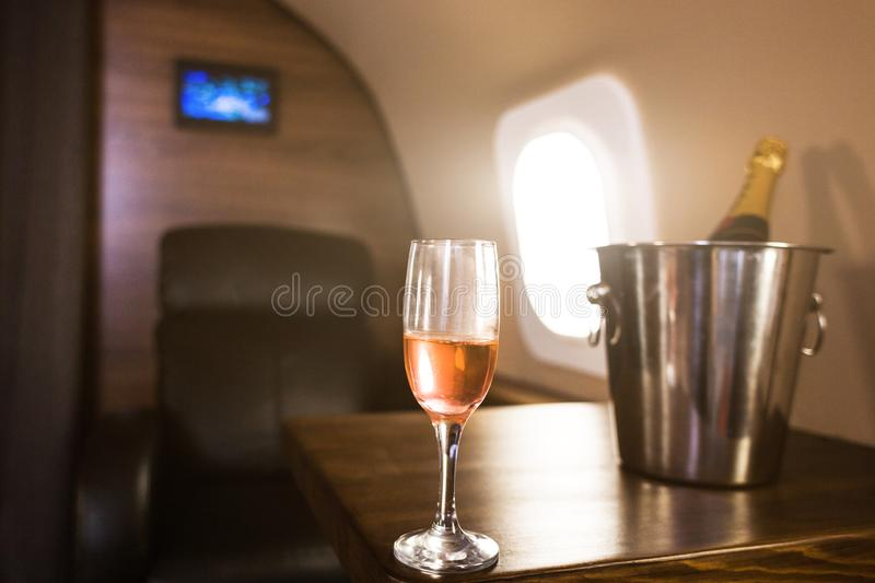 A glass of champagne in the interior of a private jet. Flying first class.  royalty free stock photos