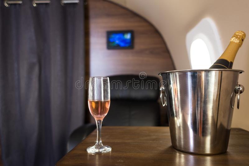 A glass of champagne in the interior of a private jet. Flying first class.  stock image
