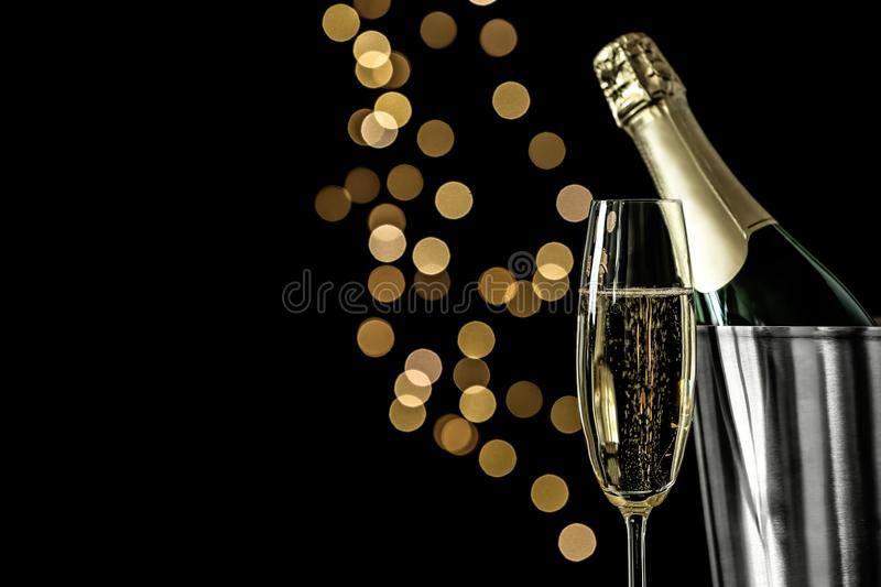 Glass of champagne near bucket with bottle against blurred lights. Space for text royalty free stock photo