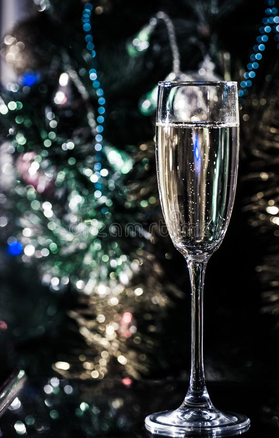 A glass of champagne under the Christmas tree royalty free stock image