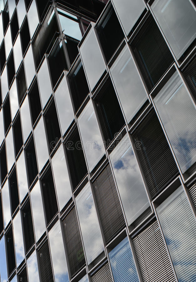 Glass checkers. Modern architecture building reflecting the sky windows with window blinds, checkerboard pattern royalty free stock image