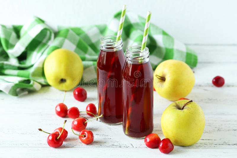 Glass of cherry juice. With apple on white wooden background stock image