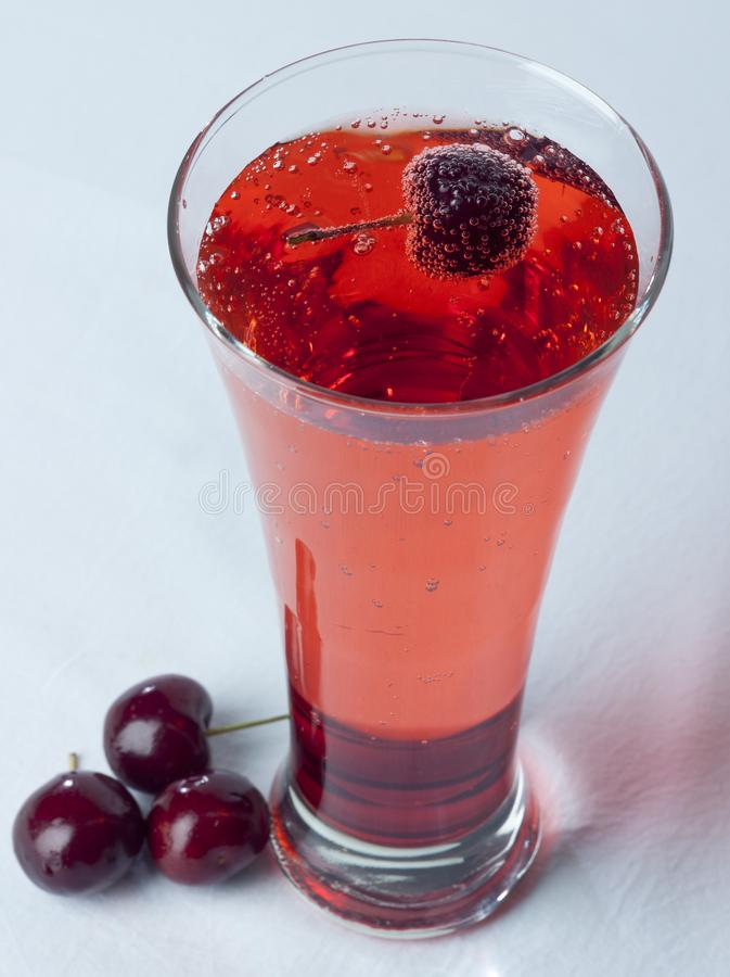A glass of Cherry Juice close up with cherry fruit and Bubles royalty free stock photography
