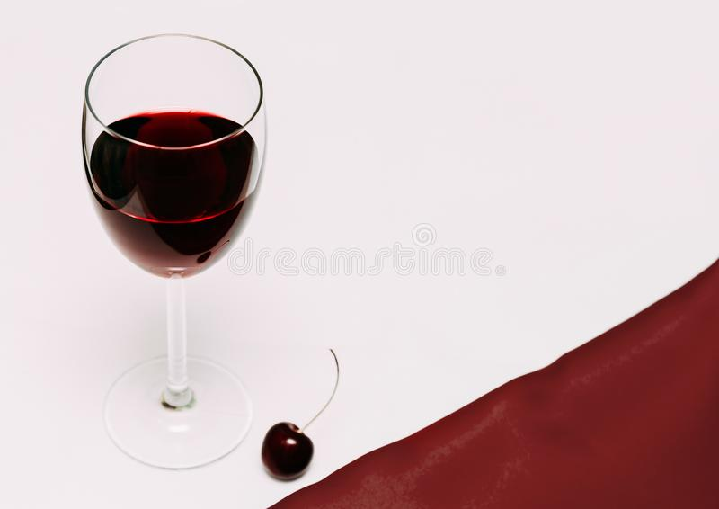 A glass of cherry wine on a red and white background and cherry berries royalty free stock photo
