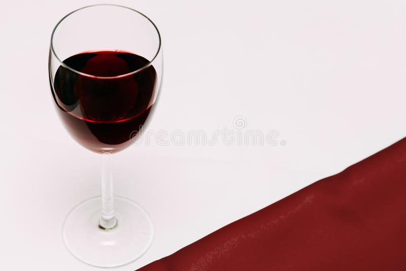 A glass of cherry wine on a red and white background and cherry berries royalty free stock photos