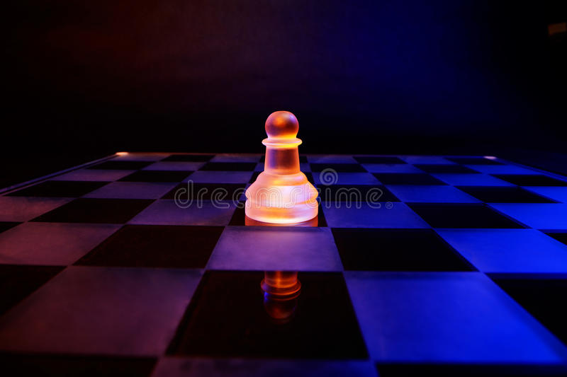 Glass chess on a chessboard lit by blue and orange light. Glass chess on a chessboard lit by colorful blue and orange light placed on a dark background stock photos