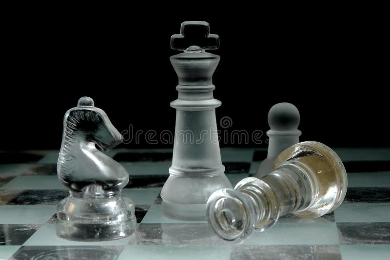 Glass Chessboard. King survives Queen's attack. A glass chessboard with a dark background royalty free stock photography