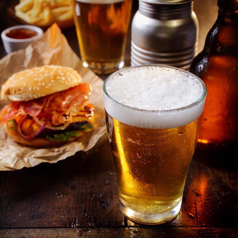 Glass of chilled beer with a hamburger. Glass of chilled beer served with a cheeseburger and French fries for a relaxing lunch in a pub or bar stock photos