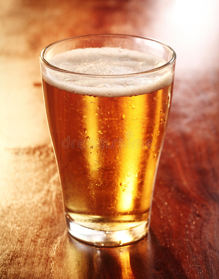 Glass of chilled golden lager or beer stock photo