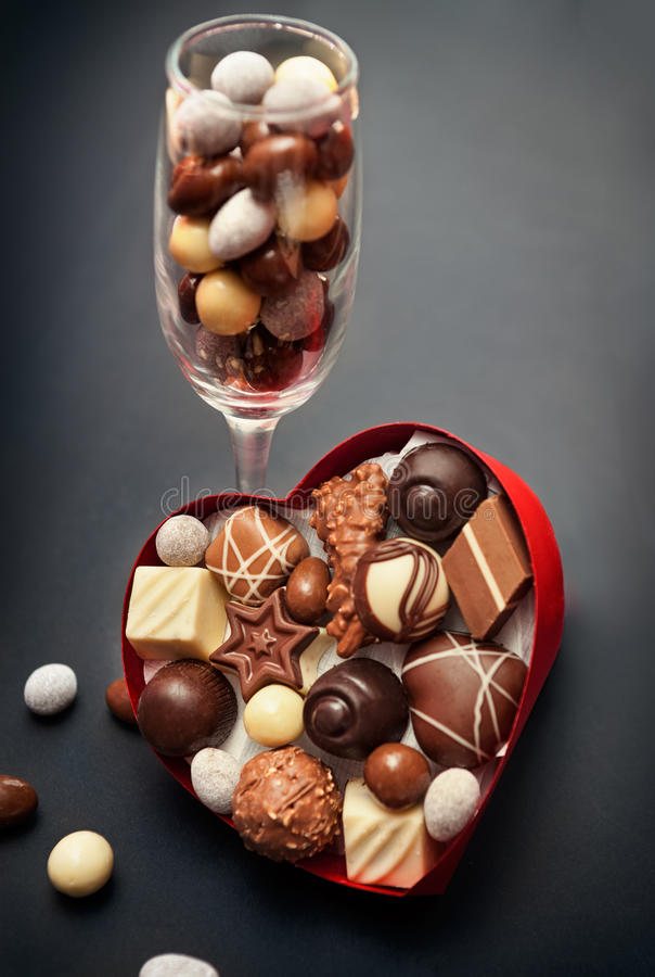 Glass with chocolate pralines and heart shaped box with pralines stock images