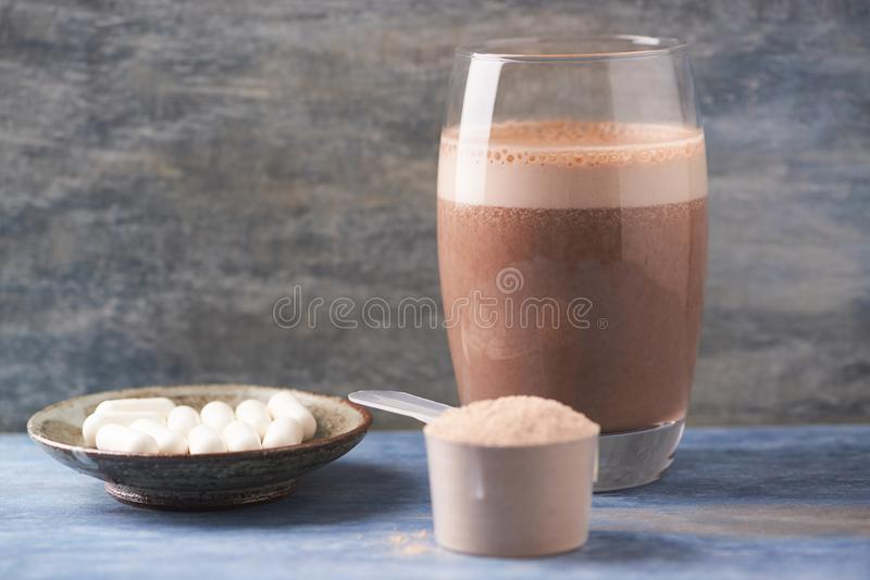 Glass of Chocolate Protein Shake with milk and banana. Whey protein in scoop and BCAA amino acids in background. Sport nutrition. Wooden background. Copy space royalty free stock photos