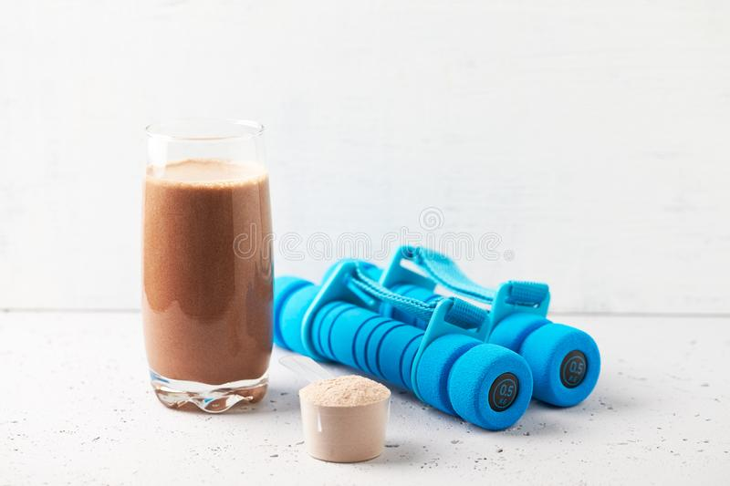 Glass of Chocolate Protein Shake with milk and banana, Whey protein in scoop and dumbbells. Sport nutrition. royalty free stock image