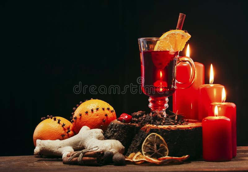 Glass of christmas hot mulled wine on wooden table with species ,oranges red candles against black background.Copy space stock image