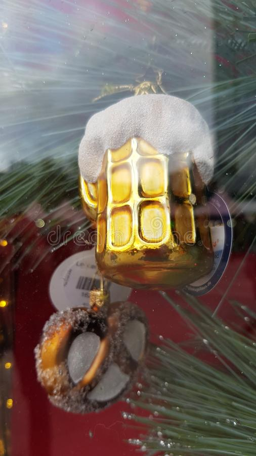 Glass Christmas ornaments in shapes of shiny golden beer mug with pretzel. Winter holiday decor. Christmas glittering decorations. royalty free stock photo