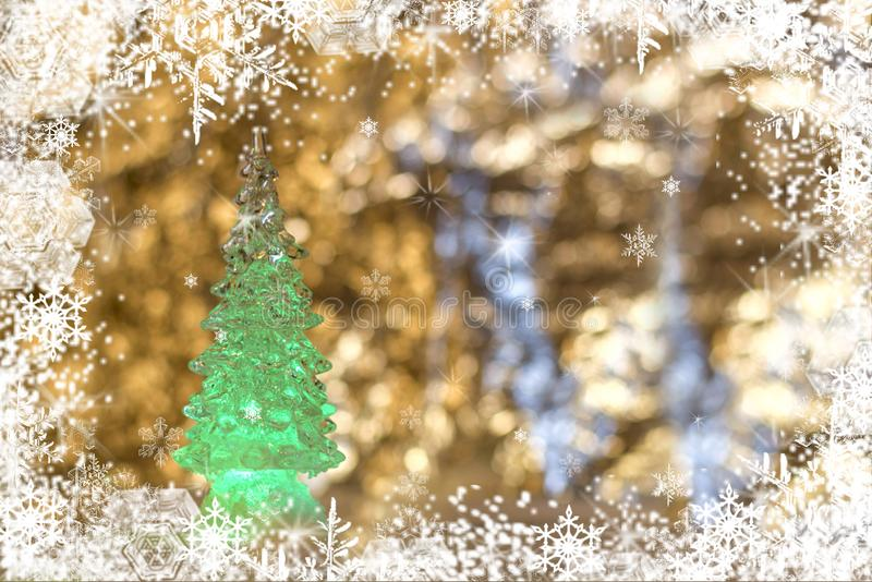 A glass Christmas toy, a green Christmas tree on a snow golden blurred background stock photos