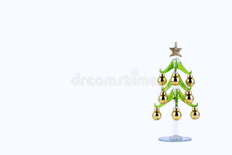 Glass christmas tree with balls and star on a light background. stock photography