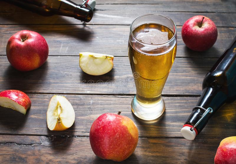 Glass of cider with apples and bottle on rustic wooden background.  stock photo