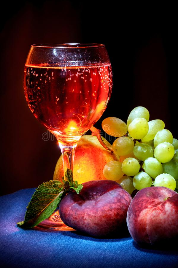 A glass of cider on with peaches and grapes royalty free stock image