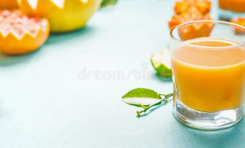 Glass of citrus fruits juice on light blue table background with various ingredients. Source of Vitamin C. Refreshing homemade. Breakfast beverages. Vitamin royalty free stock images