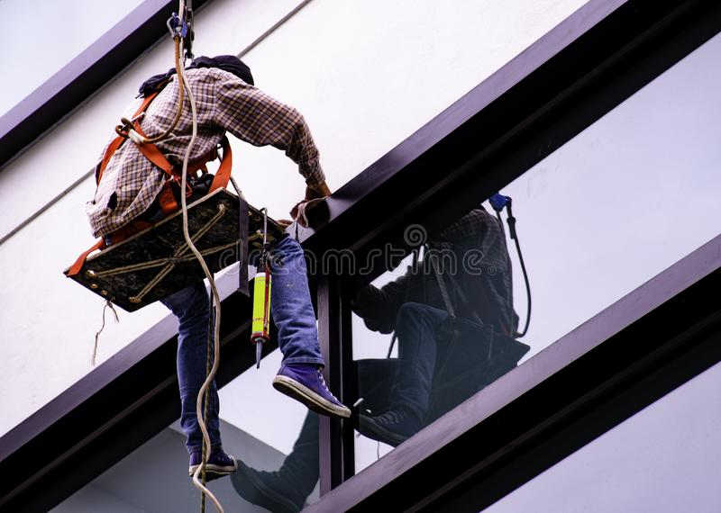 Glass cleaner. Cleaning the outside of the high building royalty free stock photos