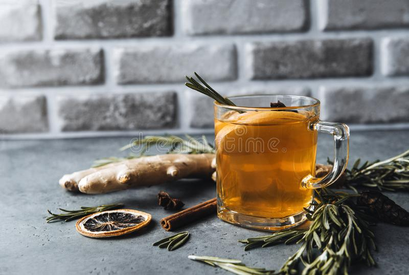 Glass clear Cup of fruit tea with cinnamon stick, rosemary, ginger, dried orange slice on grey background. 1 glass clear Cup of fruit tea with cinnamon stick royalty free stock photos