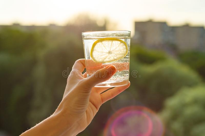 Glass of clear, sparkling water with lemon in hand. Background sky, silhouette of the city, sunset stock photo