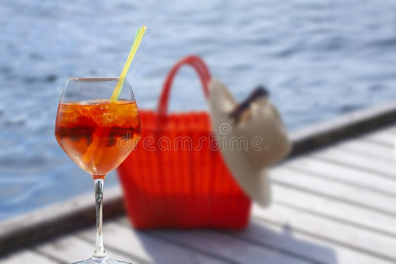 A glass of cocktail in front of blurred red braided bag with a straw hat and sunglasses placed on a wooden boardwalk royalty free stock photos