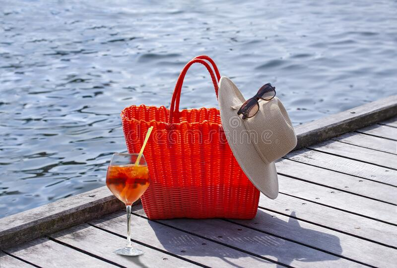 A glass of cocktail in front of a red braided bag with a straw hat and sunglasses placed on a wooden boardwalk royalty free stock photos