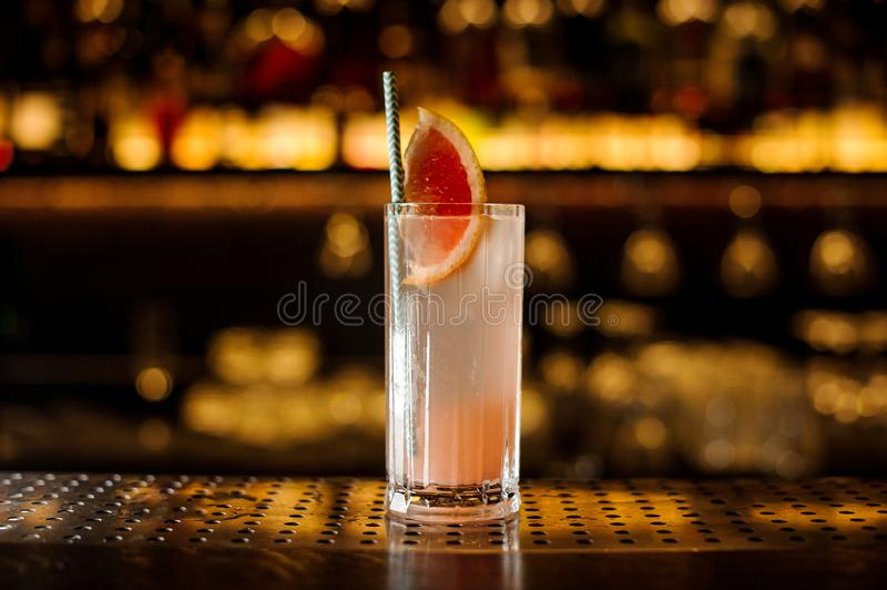 Glass of a cocktail with grapefruit on the wooden steel bar counter royalty free stock photos