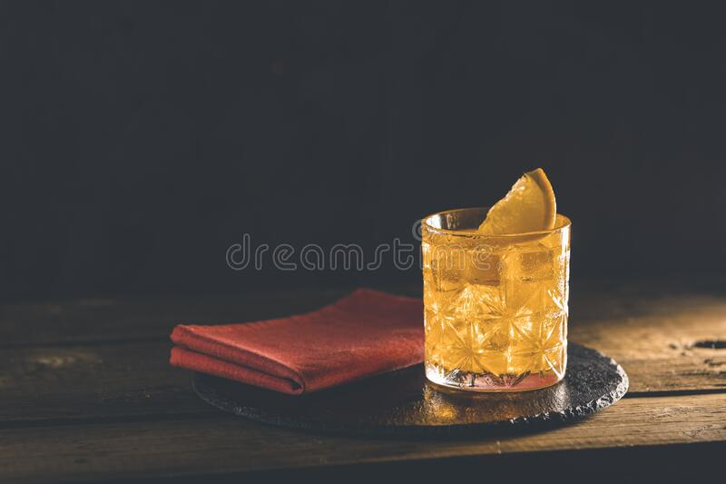 Glass of the cocktail negroni with red napkin and black stone tray on a old wooden board. Decorated orange slice. Nice romantic stock photography