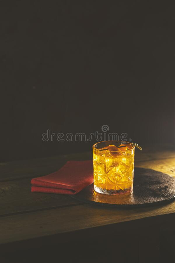 Glass of the cocktail negroni with red napkin and black stone tray on a old wooden board. Drink with gin, campari martini rosso stock image
