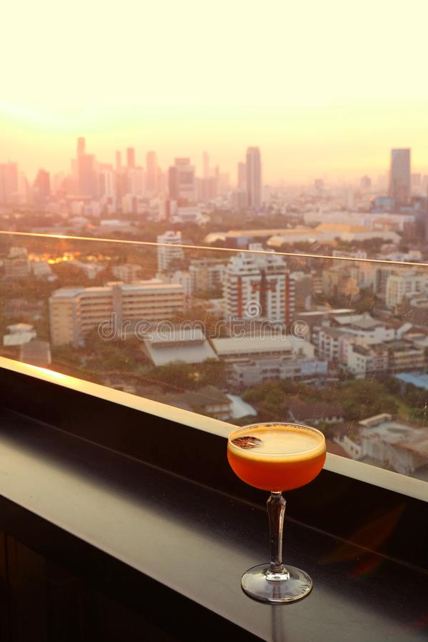 Glass of cocktail on the rooftop bar`s table with aerial urban view in background royalty free stock photo