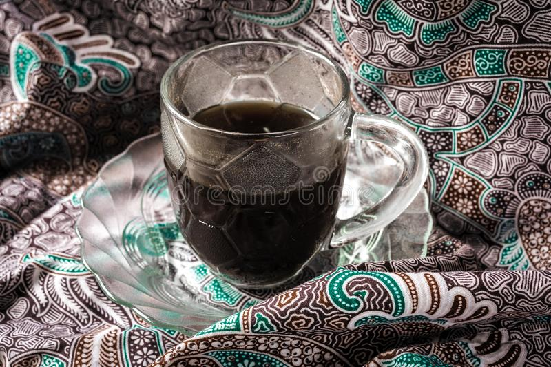 a glass of coffee isolated batik fabric background stock photos