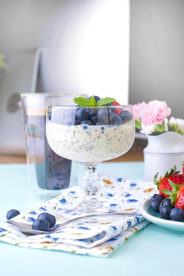 A glass of coffee and pudding chia with blueberries and strawberries for breakfast. Vegetarian healthy food. The flowers in the. Vase. Blue background. Napkin royalty free stock photography
