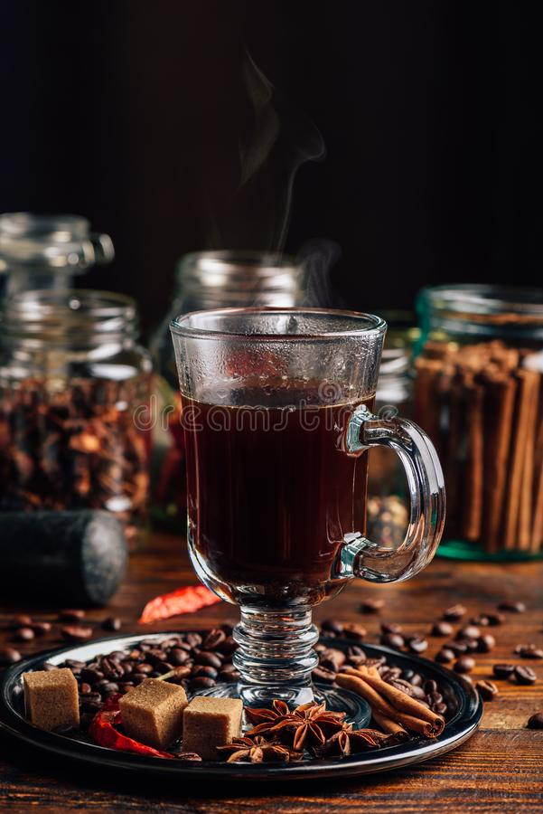 Glass of Coffee with Steam. Coffee Beans, Refined Sugar, Star Anise, Cinnamon Stick and Chili Pepper on Tray royalty free stock image