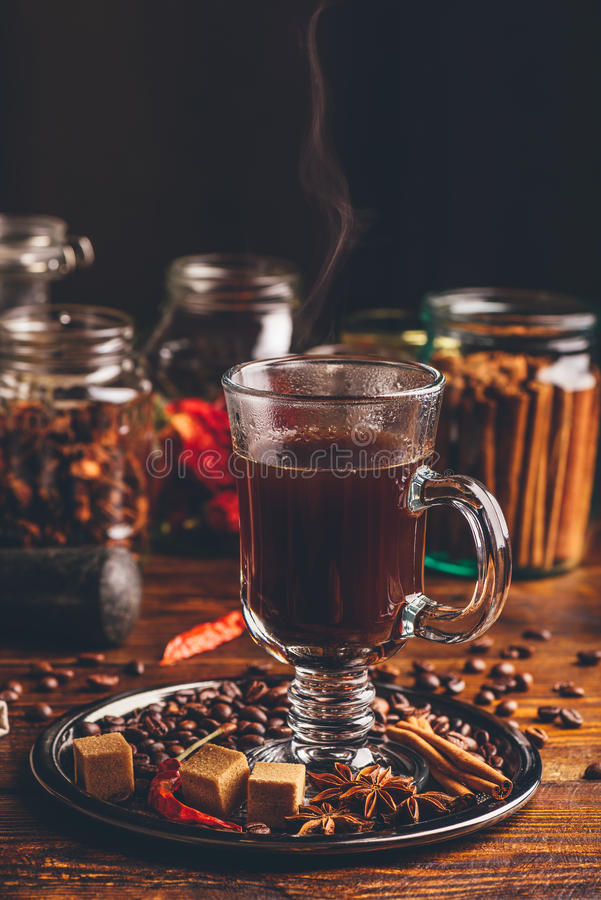 Glass of Coffee with Steam. Coffee Grains, Refined Sugar, Star Anise, Cinnamon Stick and Chili Pepper on Tray stock images