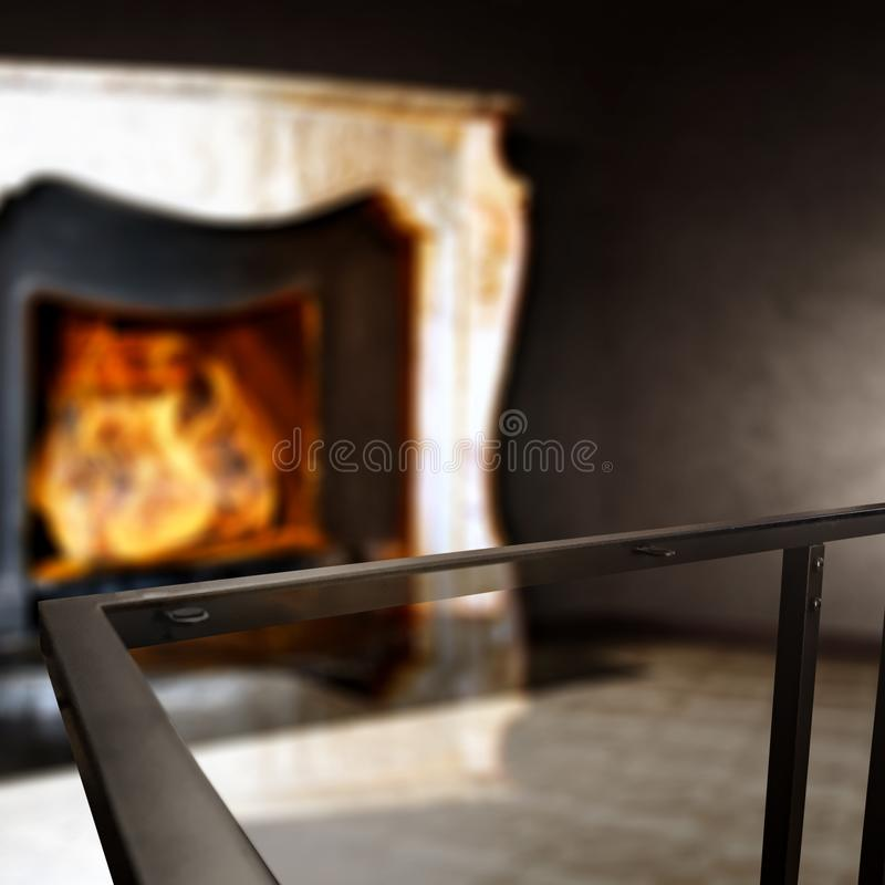 Glass coffee table top with a blurred fireplace and home interior background. Empty space for your products and decoration. Glass table top with a blurred home royalty free stock photography