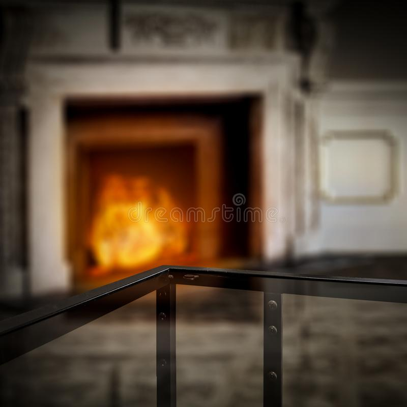 Glass coffee table top with a blurred fireplace and home interior background. Empty space for your products and decoration. Glass table top with a blurred home stock photos