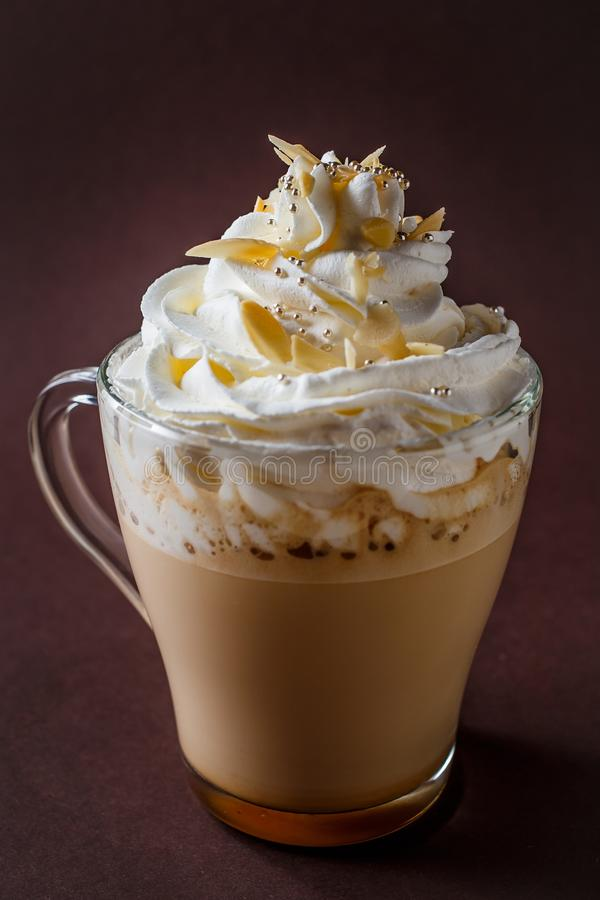 Glass of coffee with whipped cream and almonds shaving on elegant dark brown background royalty free stock photo