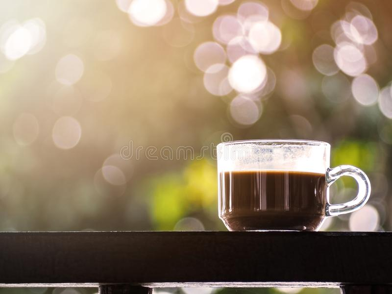 Glass of coffee on wooden table over green abstract background stock images