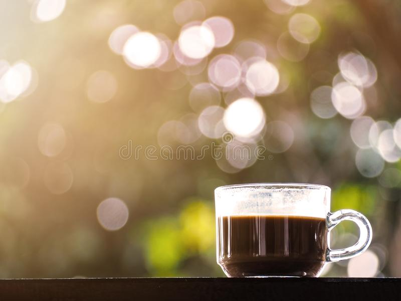 Glass of coffee on wooden table over green abstract background stock photo