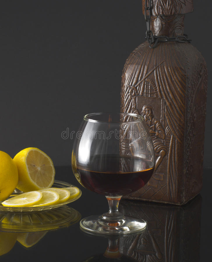Glass of cognac, bottle and lemon stock image