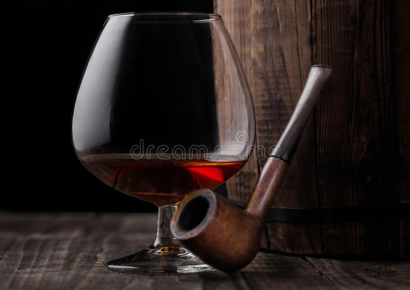 Glass of cognac brandy drink and vintage smoking pipe next to wooden barrel. Glass of cognac brandy drink and vintage smoking pipe next to wooden barrel on stock image