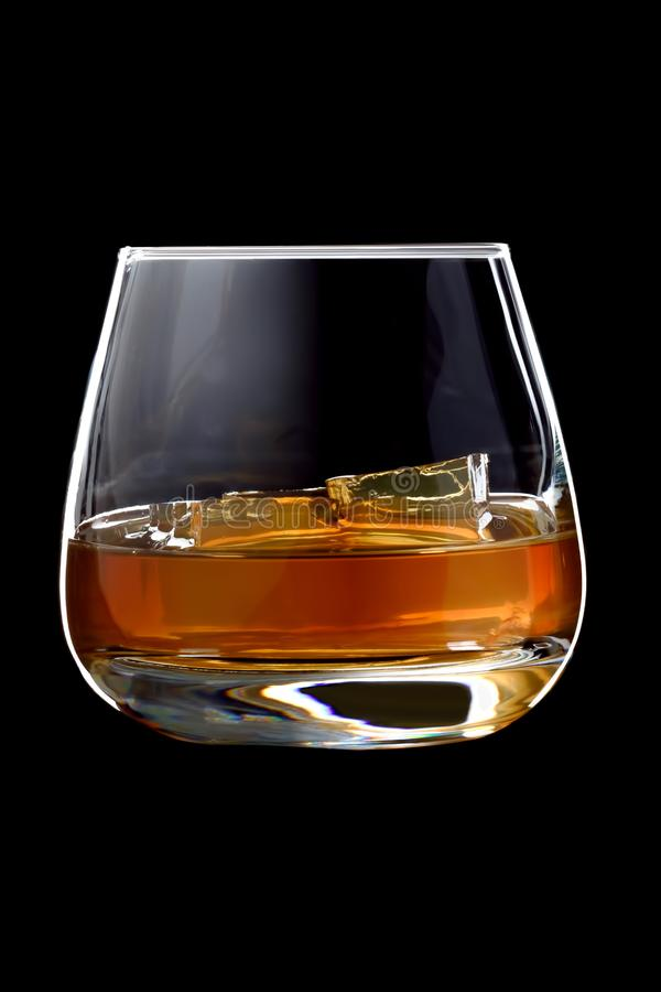 The glass of cognac or brandy with ice. The glass of cognac or brandy with ice isolated on a black background stock photo
