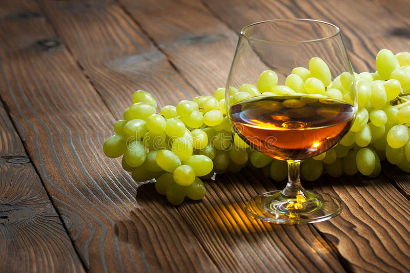 Glass of cognac and bunch of grapes royalty free stock photos