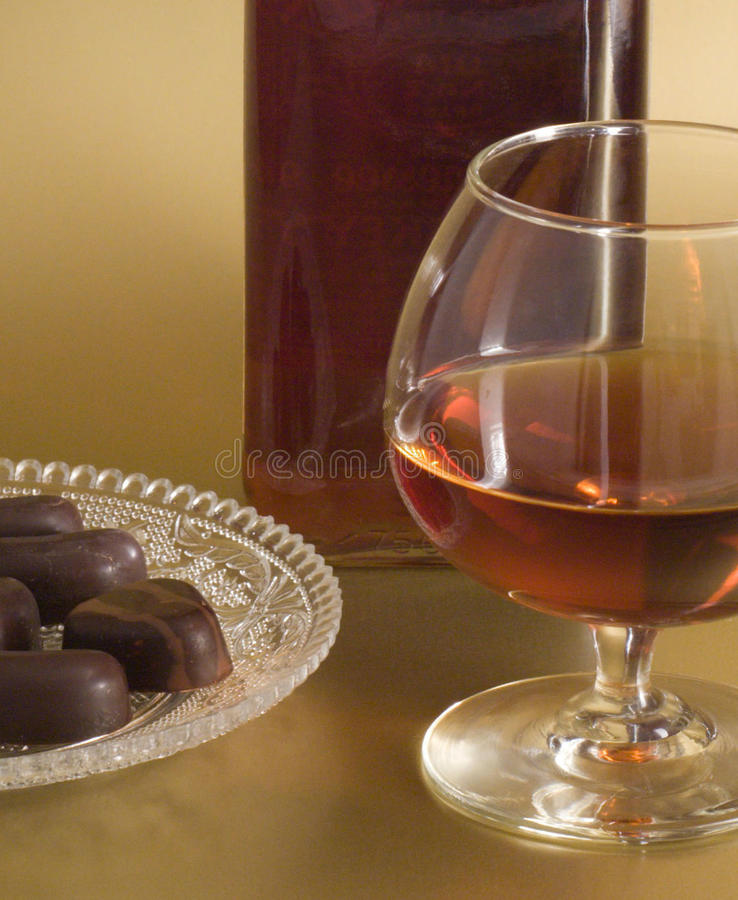 Glass of cognac with chocolate royalty free stock images