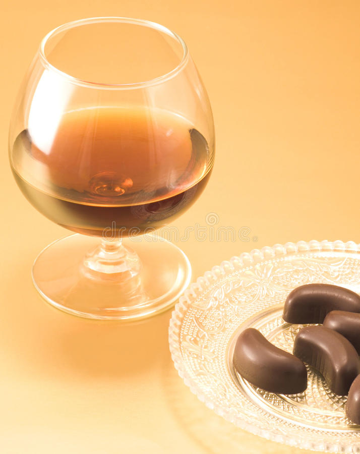 Glass of cognac with chocolate royalty free stock photography