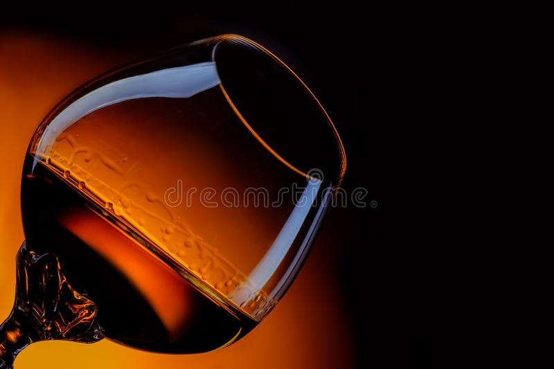 Glass of cognac close up in front of dark gradient background stock images